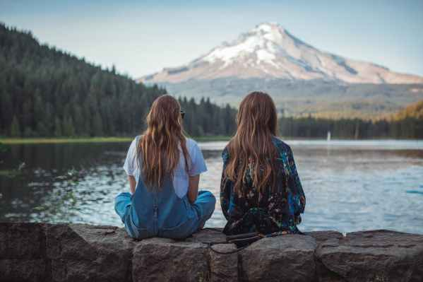 two women sitting on rock facing on body of water and mountain